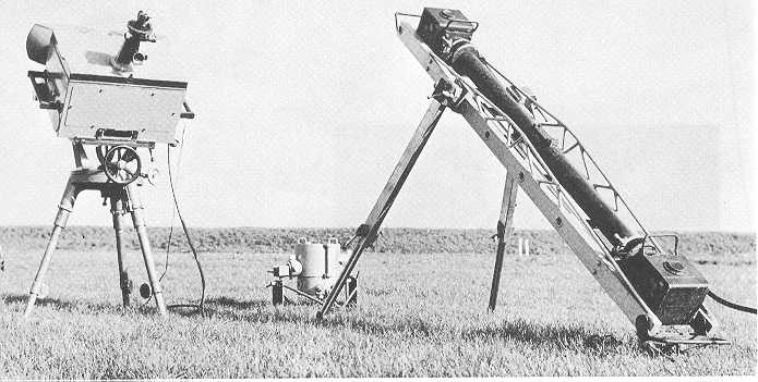 The photo bar on tripod (right), a Doppler radar, and tailstock for measuring projectile velocities under elevation