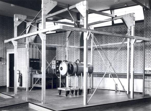 Opstelling voor het magnetisch onderzoek aan zeemijnen met zogenaamde Helmholtz spoelen in de zes ramen (ook in de vloer). Met de spoelen kan in het centrum van de ruimte van het a-magnetisch lab een magneetveld van instelbare grootte en richting worden opgewekt.