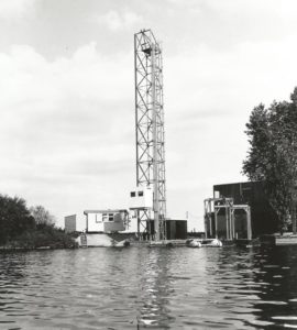 Waterside view of the facility: the lift with the radar measuring cabinet on the tower, the shed, and the raft with hoist